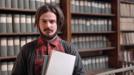 archívum : Smiling student standing before archive bookshelves, bearded boy in gray sweater and checked red shirt holding books, portrait shot in old university library Stock mozgókép