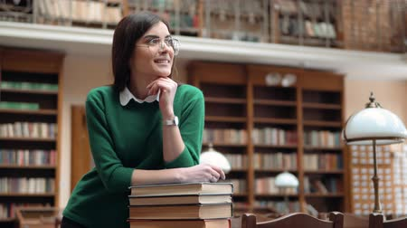 livros didáticos : Portrait of successful student in library, attractive girl dreaming as leaning joyfully on books, wearing green sweater and dark blue jeans, indoor shot in university facilities Stock Footage