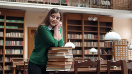 ansiklopedi : Portrait of caucasian female student in library, slender girl leaning happily on books, wearing green sweater and dark blue jeans, indoor shot in university facilities