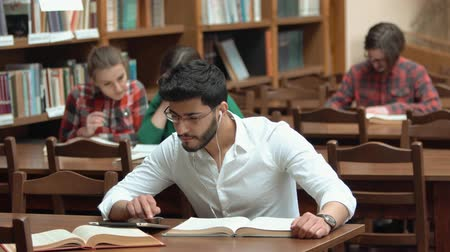 téma : Group of students revising for exam in university library, handsome bearded man using tablet as reading, two lovely girls behind discussing the topic, concentrated boy in checked shirt learning on his own