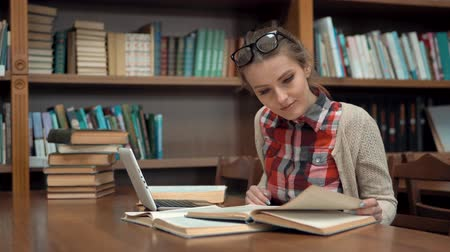 livros didáticos : Smiling caucasian girl studying in library, doing research with pleasure with use of the internet and books, wearing checked casual shirt and glasses on the head, concept of positive attitude to education