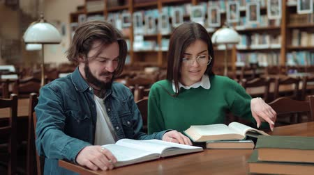 ansiklopedi : Two intellectual teenagers are reading together, discussing information as turning the pages, lovely long-haired girl wearing green sweater and stylish glasses, bearded boy - blue shirt and white t-shirt Stok Video