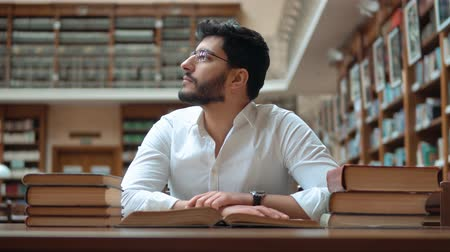 ansiklopedi : Bright student got tired, well-built man in elegant white shirt reading book in the library after classes, concept of tiredness
