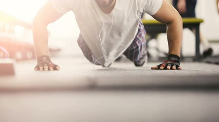 retouched : Bearded man in white t-shirt doing pushup workout on the floor in the gym