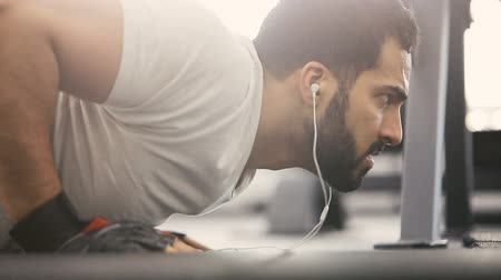 разорвал : Closeup of bearded man in white t-shirt with headphones doing pushup workout on the floor in the gym