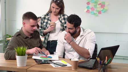 delgado : Slender caucasian girl brings collection of pictures to male colleagues, discussing done work together at brown square table Stock Footage