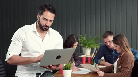 inventing : Handsome asian man working with pleasure on silver laptop, standing joyfully before group of office workers inventing brand improvement ideas