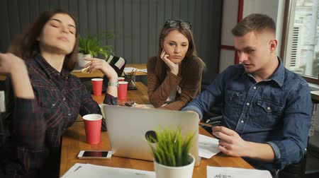 bitki : Fair-haired man in denim blue shirt informing female colleagues about main concept of the project, two attractive women sitting nearby and listening to the explanation attentively, concept of cooperation Stok Video