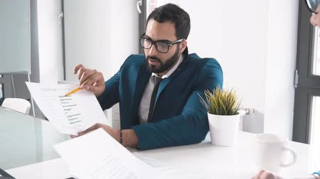 son teslim tarihi : Bearded handsome man explaining data to smart attractive woman, wearing dark blue suit and elegant black tie, pointing at the document with yellow pen during morning meeting, slowmotion in modern it company