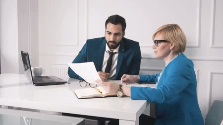kravata : Successful businesswoman holding a sheet with data, intelligent colleague looking at the chart, discussing best solution for the task, wearing expensive business suits, slowmotion of working environment