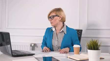 ing és nyakkendő : Satisfied blond woman dealing with documents at white square desk, wearing marine blue jacket and striped shirt, using black laptop while working, slowmotion