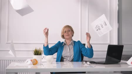 marine technology : Tired businesswoman throwing paper into the air, sitting at white square desk before black laptop, wearing marine blue jacket and striped shirt, indoor shot in modern it company Stock Footage