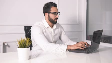 entellektüel : Intellectual and attractive businessman gets tired as working at the black laptop, taking off fashionable round glasses while typing on the computer, wearing pristine white shirt on casual working weekday