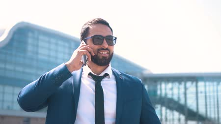 solicitor : Handsome bearded businessman wears blue suit with tie and sunglasses talking by phone before modern building of airport, success business concept Stock Footage
