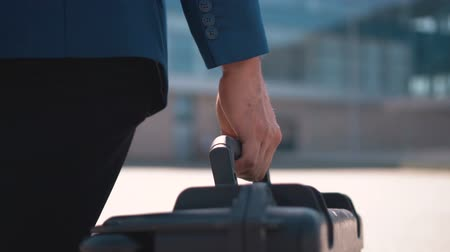 dava : Back close up view of businessman in blue suit carying black plastic trip case before modern building of airport, outdoor slowmotion Stok Video