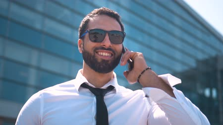 ing és nyakkendő : Bearded handsome businessman wears white shirt, tie and sunglasses talking by smartphone before modern building of airport, outdoor slowmotion