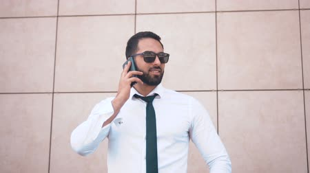 solicitor : Bearded successful businessman wearing sunglasses, white shirt and tie talking by phone before brick wall of modern building