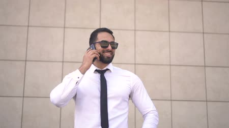 solicitor : Handsome successful businessman wearing sunglasses, white shirt and tie talking by phone before brick wall of modern building