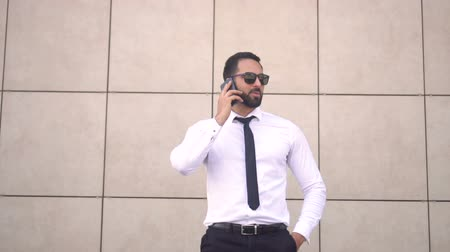 solicitor : Bearded enterpreneur wearing sunglasses, white shirt and tie talking by phone before brick wall of modern building