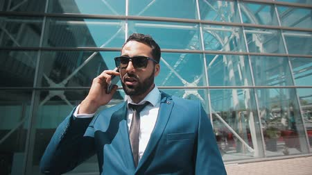 solicitor : Bearded businessman wears blue suit with tie and sunglasses starts talking by phone before modern building of airport, success business concept