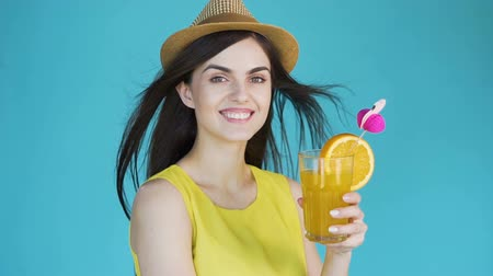 elâ : Attractive brunette holding tasty cocktail with orange, wearing straw hat and yellow summer top, slowmotion in the aqua background, concept of beach holidays Stok Video