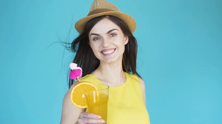 avelã : Cute dark-haired girl with orange cocktail turning joyfully, wearing sunhat and yellow summer top as posing in the aqua background, concept of summer vacation at the seaside