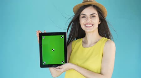 avelã : Smiling attractive woman in lovely yellow top holding a green screen tablet in the aqua background, slowmotion Stock Footage
