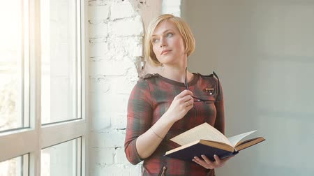 özel öğretmen : Intellectual woman in glasses reading an interesting book, standing near the window and quietly considering the information, wearing elegant checked red dress on typical working day Stok Video