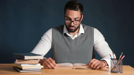 pronunciation : Good-looking black-haired man gets tired of learning english, wearing gray sweater vest and pristine white shirt, working hard at the office desk before black wall Stock Footage
