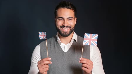 özel öğretmen : Smiling attractive man with black beard showing english flags happily, wearing gray sweater vest and smart white shirt, concept of successful english learning, isolated shot in the black background Stok Video