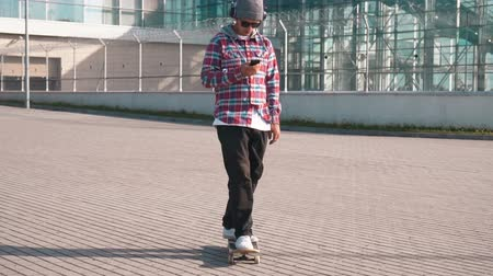 trousers : Good-looking boy in black pants and checked shirt listening to music while skateboarding, using smartphone as riding in the street in his free time Stock Footage