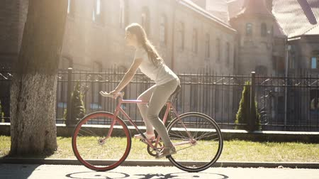 bisiklete binme : Long-haired slim brunette cycling in the sunlight, having relaxed ride near impressive historical building in old european city
