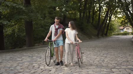 bliskosc : Cheerful couple of friends talking while going back home, walking happily after active bike ride in green local park, outdoor shot of weekend leisure activities