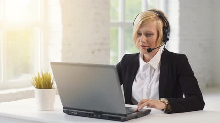 телемаркетинг : Call center operator, blonde woman dressed in black jacket and white shirt working on laptop via headset in white office against sunset windows Стоковые видеозаписи