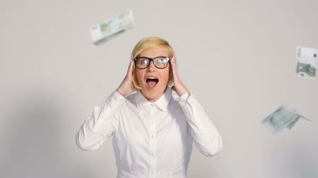 earnings : Blonde pretty woman dressed in white shirt on isolated background with falling euro banknotes in slow motion Stock Footage