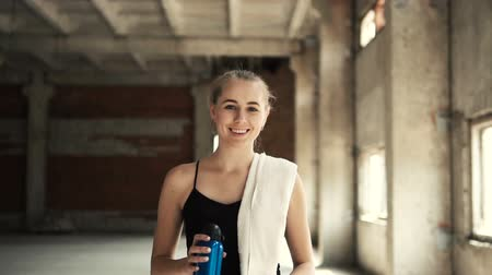 yelek : Slender fair-haired girl walking with blue bottle of water and white towel on the shoulder, giving a pleasant smile as moving, going to begin morning training, slowmotion