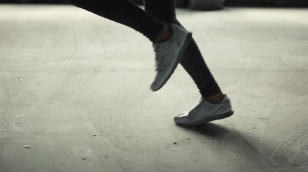 legginsy : Young slim woman jogging in white sneakers and gray legging indoors, slowmotion Wideo