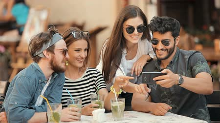 socialization : Cheerful friends look pictures over on smartphone, discussing selfie while hanging out in modern outdoor cafe Stock Footage