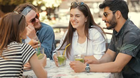 socialization : Beautiful and smiling boys and girls chatting at the table, relaxing after work on hot summer day, concept of importance of communication for well and happy human being Stock Footage