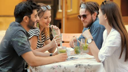 socialization : Happy and successful boys and girls hanging out in downtown, lifting up glasses of delicious, cold lemonade to drink, outdoor shot in summertime Stock Footage