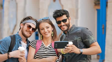 socialization : Smiling friends taking selfie with black smartphone as walking in the street, snapping photos for sweet memories, wearing stylish casual clothes on warm summer afternoon