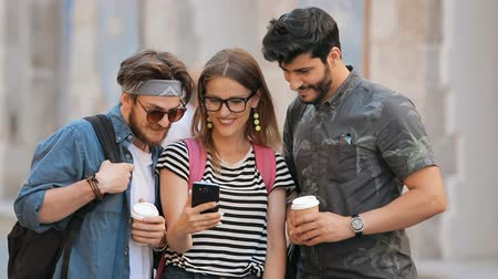 socialization : Cheerful intelligent students looking at pictures on the phone, taking a break while going for a walk in urban area