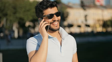tshirt : Bearded asian man talking on the phone in the street on bright summer day, wearing black sunglasses and white t-shirt, chatting joyfully as waiting for a meeting