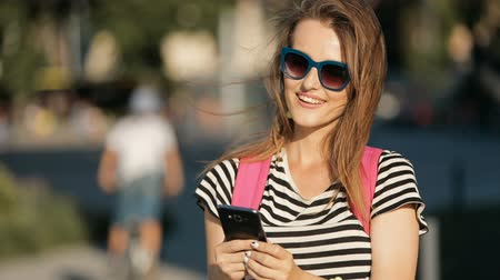 bilezik : Excited fair-haired girl in attractive sunglasses texting a message on black smartphone, standing in the crowded street on warm sunny day, concept of virtual communication