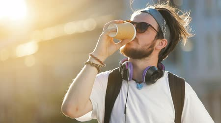 футболки : Good-looking young man drinking coffee in the street in beautiful sunlight, giving a smile while enjoying the drink, wearing black backpack and white t-shirt, takes time to enjoy the moment in hectic urban lifestyle