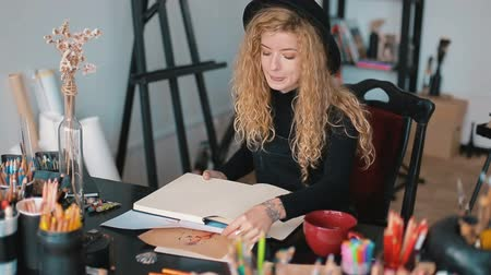 шедевр : Professional artist working at the desk full of coloured pencils, having a mug of tea while drawing a sketch in the album, artistic working atmosphere, indoor