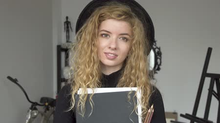 шедевр : Portrait of young female painter, pretty smiling girl with gorgeous curly hair standing in the middle of the art studio, holding big sketchbook and pencils