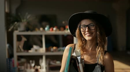 glass master : Portrait of smiling artist, tall and slim woman holding big picture and different paintbrushes, wearing elegant black hat and denim jumpsuit, indoor shot in modern art studio Stock Footage