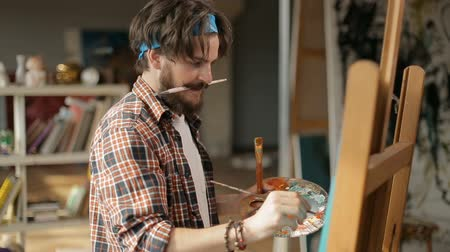 шедевр : Mad creative painter with fair beard and moustache painting a picture, transferring conceived idea on canvas, working with great pleasure in modern art studio Стоковые видеозаписи