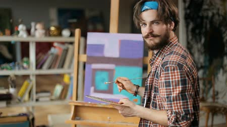 şaheser : Portrait of smiling caucasian painter, fair haired man painting orange line on aqua background, working on modern piece of art at easel in small art studio Stok Video